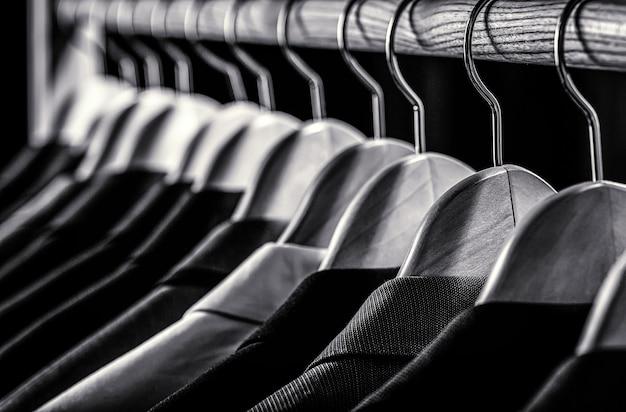 Herrenhemden, anzug hängt am gestell. schwarz und weiß.