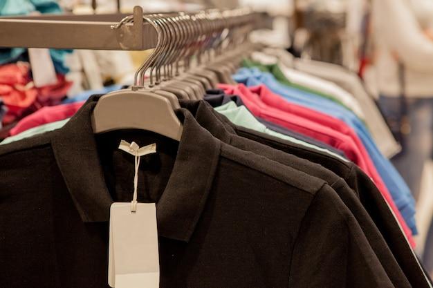 Herrenhemden in verschiedenen farben auf kleiderbügeln in einem einzelhandelsgeschäft.