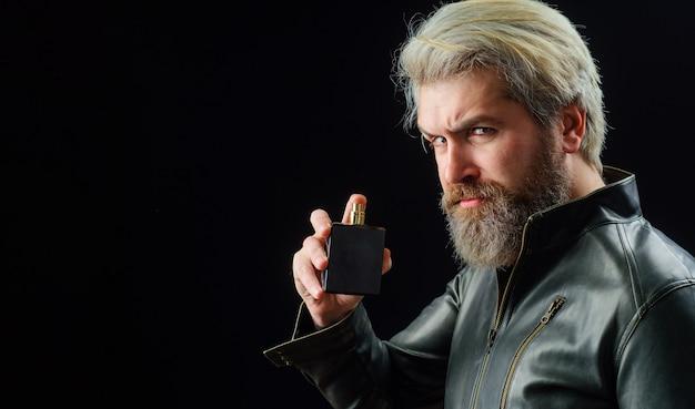 Herrenkosmetik. bärtiger mann mit parfüm- oder kölnischwasserflasche. männlicher duft und parfümerie. platz kopieren.