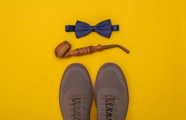 Herrenschuhe, pfeife und fliege auf gelbem hintergrund. herren accessoires. ansicht von oben