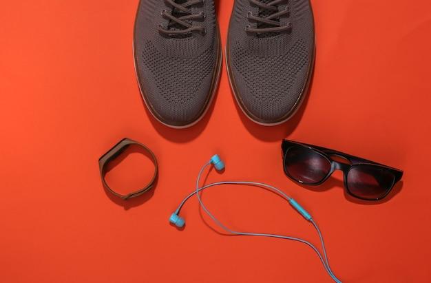 Herrenschuhe und gadgets (smart bracelet, kopfhörer), sonnenbrille auf orangem hintergrund. ansicht von oben