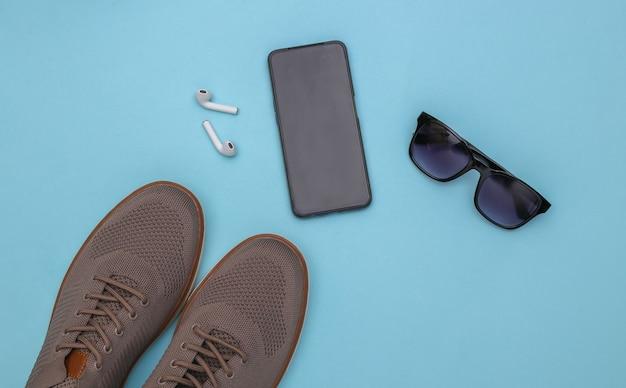 Herrenschuhe und gadgets (smartphone, kopfhörer), sonnenbrille auf blauem grund. ansicht von oben
