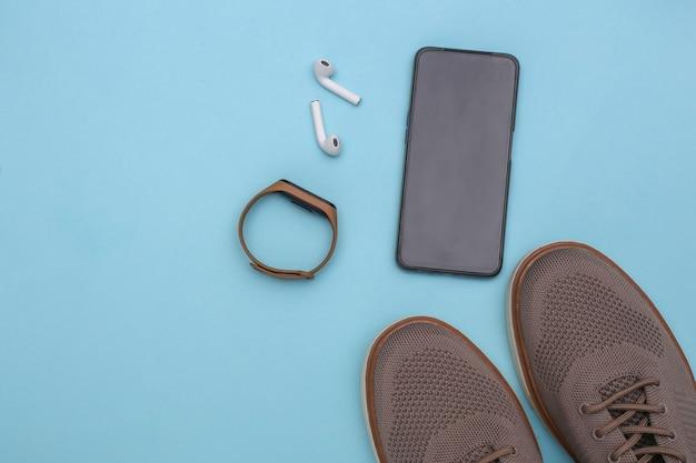 Herrenschuhe und gadgets (smartphone, smart bracelet, kopfhörer) auf blauem hintergrund. ansicht von oben