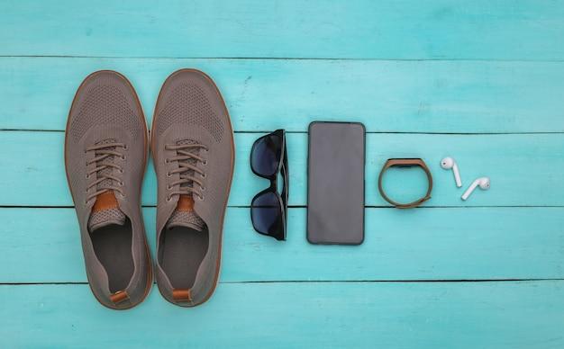 Herrenschuhe und -geräte (smartphone, smart-armband, kopfhörer), sonnenbrille auf blauem holzhintergrund. ansicht von oben