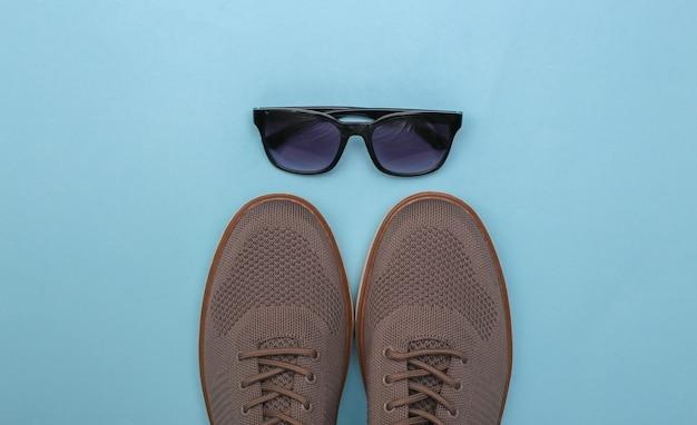 Herrenschuhe und sonnenbrillen auf blauem grund. ansicht von oben