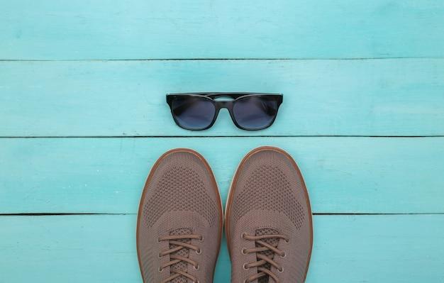 Herrenschuhe und sonnenbrillen auf blauem holzhintergrund. ansicht von oben