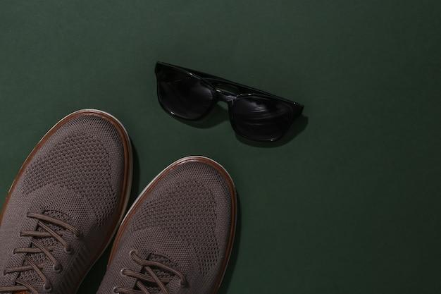 Herrenschuhe und sonnenbrillen auf grünem hintergrund. ansicht von oben