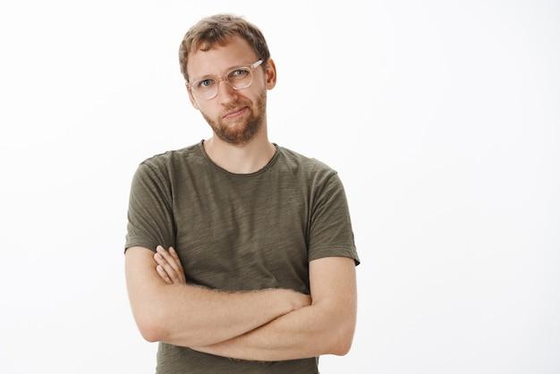 Herrischer kluger und kreativer unzufriedener geschäftsmann im dunkelgrünen t-shirt und in der brille, die kopf neigt und vor unzufriedenheit grinst, die hände auf der brust kreuzend, neues konzept ablehnend