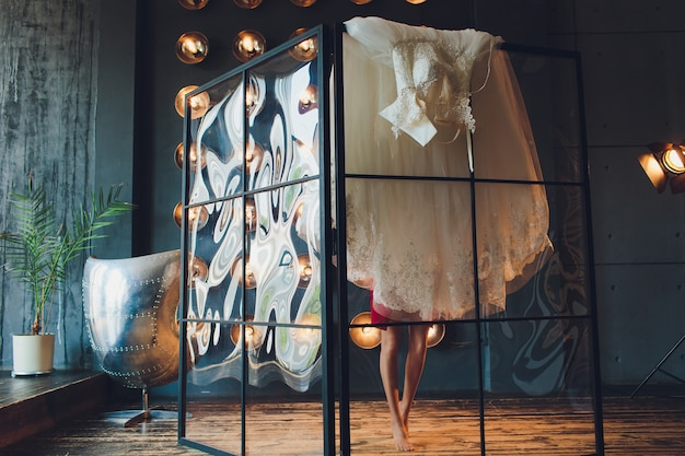 Herrlich, wird braut im weißen luxuskleid zur hochzeit fertig. morgenvorbereitungen. frau kleid anziehen.