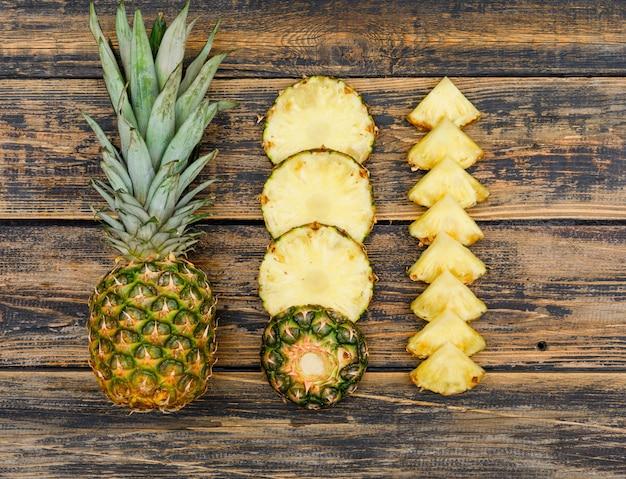 Herrliche ananasscheiben auf altem holzschmutz. draufsicht.