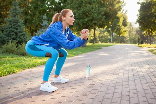 Herrliche athletische frau, die morgens im park ausarbeitet