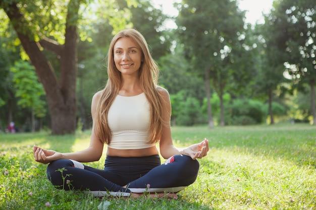 Herrliche athletische frau, die yoga am park tut