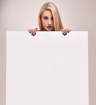 Herrliche blonde frau, die eine unbelegte anschlagtafel anhält