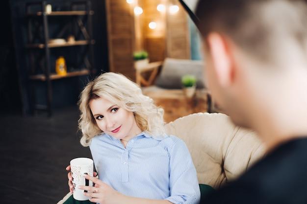 Herrliche blonde freundin, die am trainer gegen ihren freund sitzt.