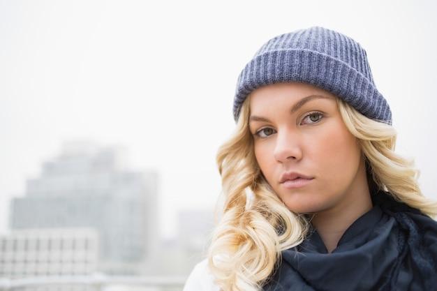 Herrliche blondine in der winterkleidung, die draußen aufwirft