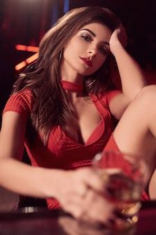 Herrliche brunettefrau im roten kleid mit glas whisky