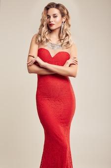 Herrliche elegante blondine, die rotes kleid der mode tragen