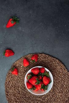 Herrliche erdbeeren in einer weißen schüssel auf einem runden tischset und grauem schmutzhintergrund. flach liegen.