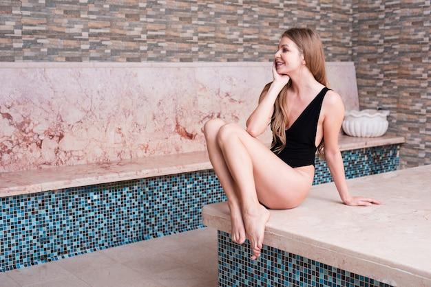 Herrliche frau, die am badekurort aufwirft