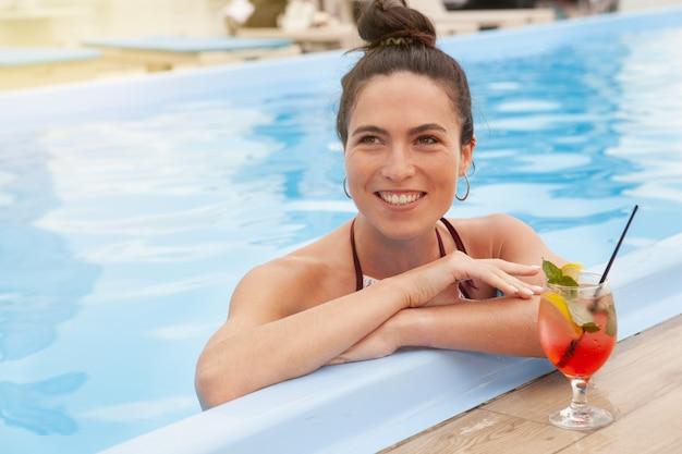 Herrliche frau, die am swimmingpool sich entspannt