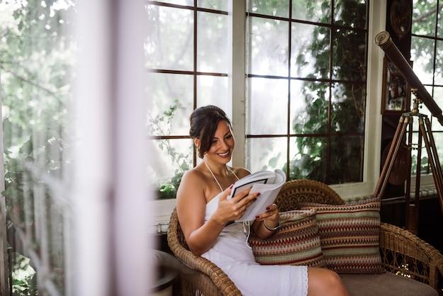 Herrliche frau, die ein buch in der gartensonne oder im wintergarten liest.