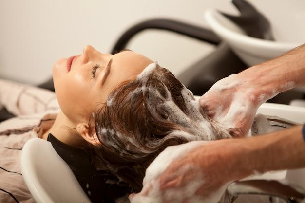 Herrliche frau, die ihr haar vom friseur waschen lässt