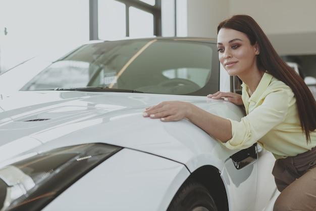 Herrliche frau, die neues auto an der verkaufsstelle kauft