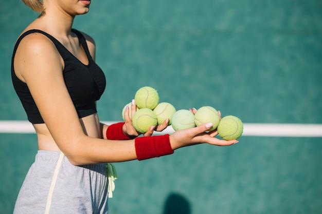 Herrliche frau, die tennisbälle hält