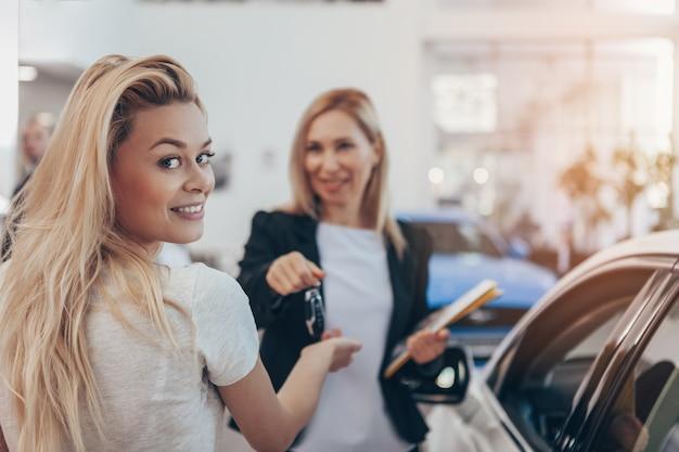 Herrliche frau, die zur kamera empfängt autoschlüssel zu ihrem neuen automobil an der verkaufsstelle lächelt.