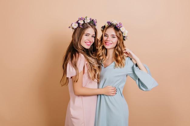 Herrliche frau im rosa kleid, die vergnügen während fotoshooting mit bester freundin ausdrückt