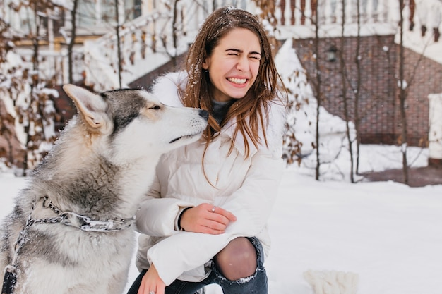 Herrliche frau im weißen kittel, die winterspaziergang mit ihrem lustigen hund genießt. außenporträt der reizenden europäischen frau, die mit husky am schneebedeckten hof spielt.