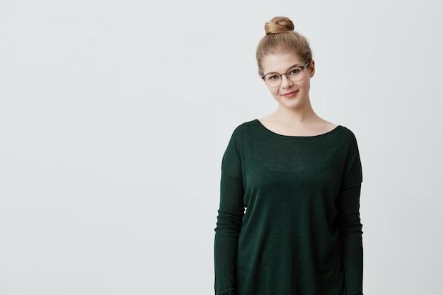 Herrliche frau in stilvoller brille, trägt grünen losen pullover, steht drinnen, lächelt glücklich. kaukasisches mädchen mit blonden haaren im knoten sanft lächelnd. positive gefühle und emotionen.