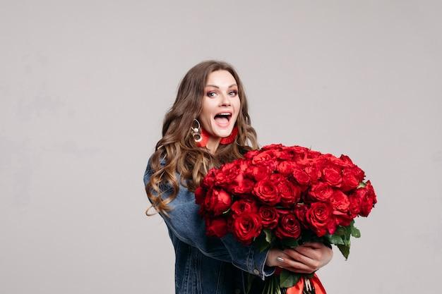 Herrliche frau mit den großen ohren, die rosen und das lächeln halten
