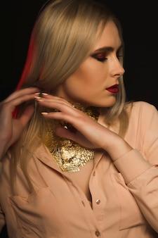 Herrliche frau mit hellem make-up und goldfolie am hals