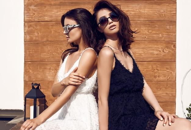 Herrliche helle paare von brunettefrauen in den schwarzweiss-kleidern