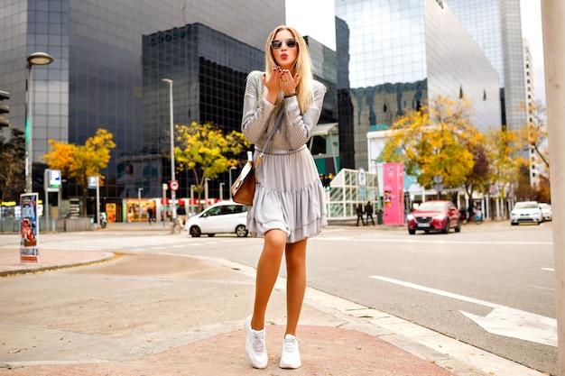 Herrliche hübsche elegante blonde frau, die weibliches trendiges kleid und pullover trägt, die luftküsse senden, volle länge, herbstfrühling-zwischensaisonzeit, tourist in new york city.