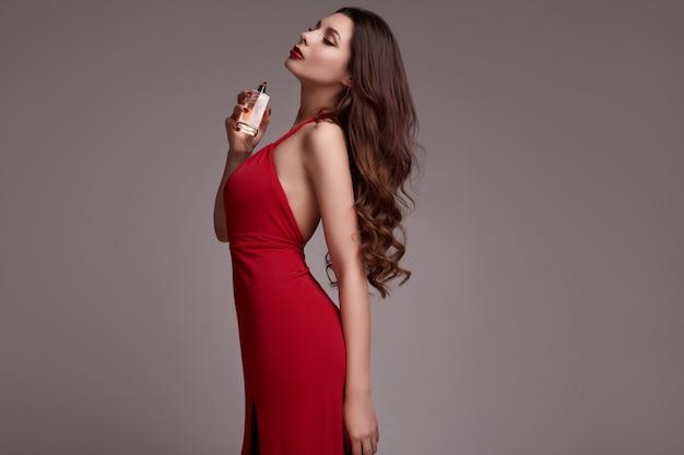 Herrliche junge brunettefrau mit dem gelockten haar im roten kleid