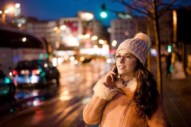 Herrliche junge frau, die am telefon in der stadtstraße, ampeln auf hintergrund spricht.
