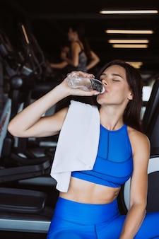 Herrliche junge frau mit einem tuch auf ihrem trinkwasser der schulter von einer flasche an der turnhalle