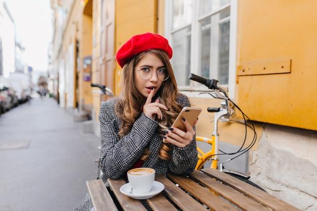 Herrliche junge kaukasische frau in der eleganten kleidung, die mit telefon im straßencafé sitzt