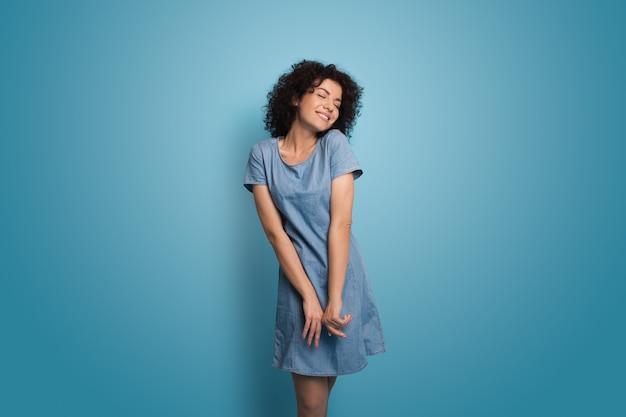 Herrliche kaukasische frau mit dem lockigen haar, das ein blaues sommerkleid trägt, lächelt an einer wand