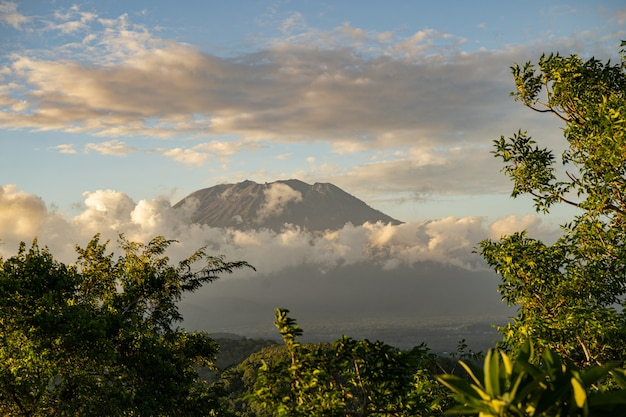 Herrliche landschaft aus grünen bäumen mit vulkan, umgeben von dichten wolken stockfoto