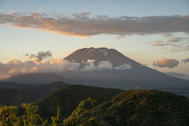 Herrliche landschaft mit grasbewachsenen hügeln und majestätischem vulkan, umgeben von wolken stockfoto