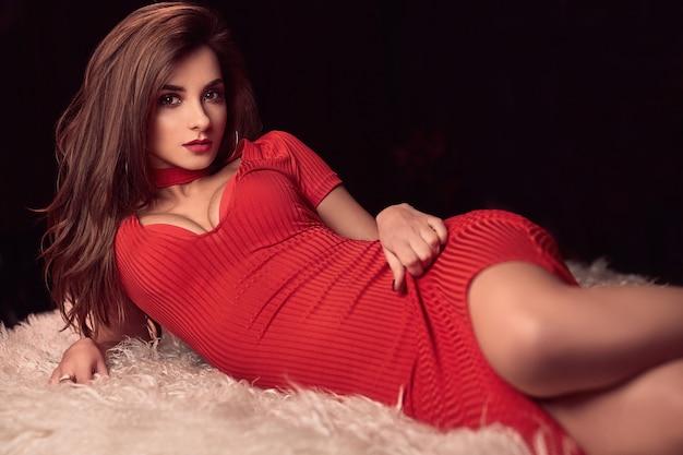 Herrliche schönheit junge brunettefrau im roten kleid auf einem weißen pelz