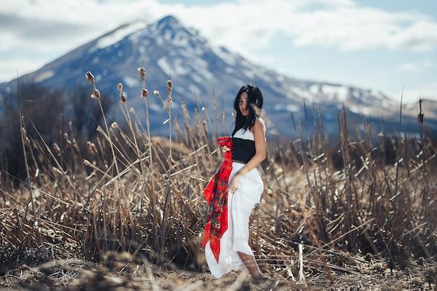 Herrlicher frau brunette in den bergen am sonnenschein und am blauen himmel mit wolken. traditionelle kleidung mit rotem tuch