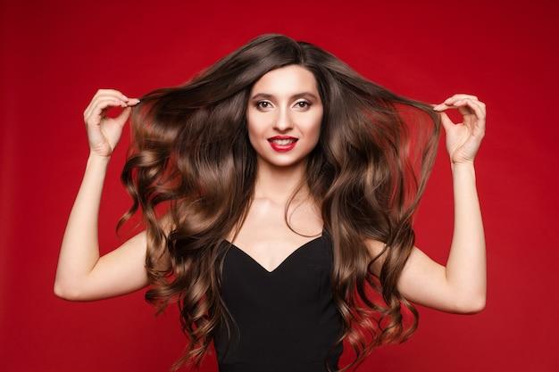 Herrlicher junger brunette mit dem idealen langen haar auf rotem hintergrund.