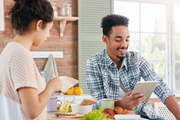 Herrlicher junger mann mit dunkler haut und lockigem haar liest lustige geschichten auf tablet-computer vor, während er gegenüber frau sitzt, die beschäftigt ist