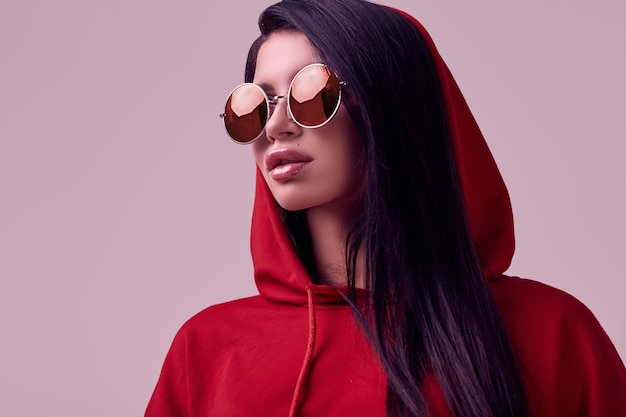 Herrlicher roter hoodie der brunettefrau in mode im studio