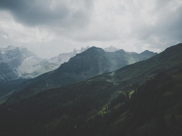 Herrlicher schneebedeckter berg unter dem schönen nebligen himmel