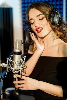 Herrlicher schöner weiblicher vokalkünstler mit geschlossenen augen singend im modernen tonstudio. porträt eines recht jungen modells, das im studio singt.